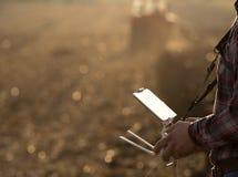 Landwirt, der Brummen über Ackerland navigiert stockfotos