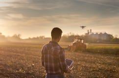 Landwirt, der Brummen über Ackerland navigiert Lizenzfreies Stockfoto