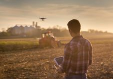 Landwirt, der Brummen über Ackerland navigiert Stockfotografie