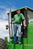 Landwirt, der in der Traktortür steht Lizenzfreies Stockfoto