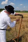 Landwirt, der die Sense schärft lizenzfreie stockfotografie