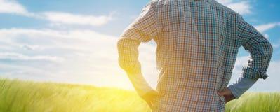 Landwirt, der die Sonne auf dem Horizont betrachtet stockfotografie