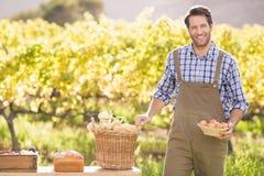 Landwirt, der einen Korb von Kartoffeln und von Eiern hält Lizenzfreie Stockfotos