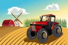 Landwirt, der einen Traktor reitet Stockbild