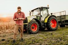 Landwirt, der an Feld unter Verwendung des Smartphone in der modernen Landwirtschaft - Traktorhintergrund arbeitet lizenzfreies stockbild