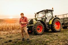 Landwirt, der an Feld unter Verwendung des Smartphone in der modernen Landwirtschaft - Traktorhintergrund arbeitet stockfotografie