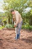Landwirt, der im Garten mithilfe einer Rührstange planiert pl arbeitet Stockbilder