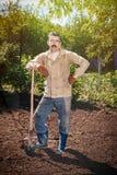 Landwirt, der im Garten mithilfe einer Schaufel gräbt t arbeitet Stockfotografie