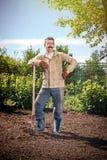 Landwirt, der im Garten mithilfe einer Schaufel gräbt t arbeitet Lizenzfreie Stockbilder