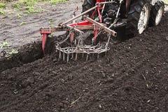 Landwirt, der Land für das Säen vorbereitet Traktor, der an dem Bauernhof, ein moderner landwirtschaftlicher Transport, arbeitend Stockfotografie