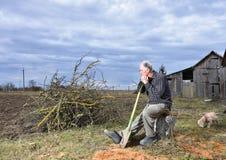 Landwirt, der mit einer Schaufel auf dem Feld sitzt Stockbild