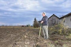 Landwirt, der mit einer Schaufel auf dem Feld steht Stockfoto