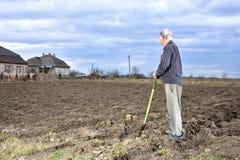 Landwirt, der mit einer Schaufel auf dem Feld steht Lizenzfreies Stockbild