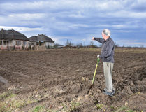 Landwirt, der mit einer Schaufel auf dem Feld steht Lizenzfreies Stockfoto