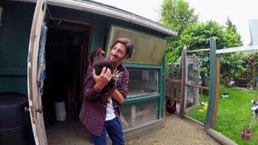 Landwirt, der mit Henne im Hühnerstall 4k spielt stock video