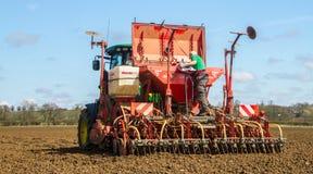 Landwirt, der oben die Drillmaschine bereit zur Bohrung lädt Lizenzfreie Stockbilder