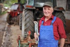 Landwirt, der seinen roten Traktor repariert Stockfotografie