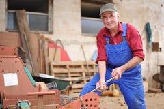 Landwirt, der seinen roten Traktor repariert Lizenzfreie Stockfotografie