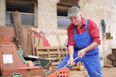Landwirt, der seinen roten Traktor repariert Lizenzfreie Stockfotos