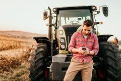 Landwirt, der Smartphone und Traktor am Ernten verwendet Moderne Landwirtschaft mit Technologie und Maschineriekonzept lizenzfreies stockbild