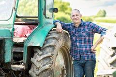 Landwirt, der Traktor in der Landschaft fährt Stockfotografie