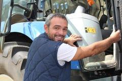 Landwirt, der in Traktor klettert lizenzfreies stockbild