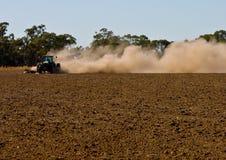 Landwirt hebt Wolken des Staubes als er pflügt sein trockenes an Lizenzfreie Stockfotografie