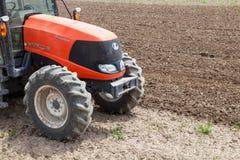 Landwirt im Traktor, der Land für das Säen vorbereitet stockbild