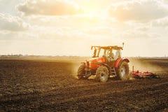 Landwirt im Traktor, der Land mit Saatbeetlandwirt vorbereitet lizenzfreies stockbild