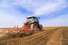 Landwirt im Traktor, der Land mit Saatbeetlandwirt vorbereitet Stockfoto
