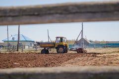 Landwirt im Traktor, der Land mit Saatbeetlandwirt vorbereitet lizenzfreie stockfotografie