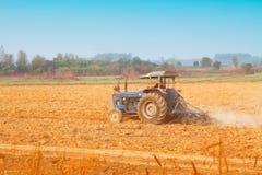 Landwirt im Traktor, der Land vorbereitet stockfotografie
