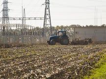 Landwirt im Traktor, der Land vorbereitet Stockfotos