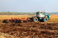 Landwirt im Traktor, der Land vorbereitet Stockbilder