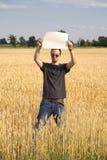 Landwirt-Kerl im Wheatfield, der unbelegtes Zeichen anhält Stockfotos