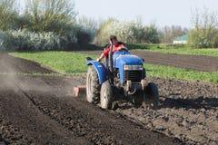 Landwirt kultiviert den Boden auf dem Traktor Stockbilder