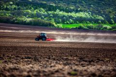 Landwirt mit dem Traktor, der Ernten am Feld sät Lizenzfreies Stockbild