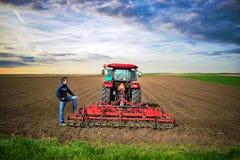 Landwirt mit dem Traktor, der Feld für das Säen vorbereitet lizenzfreie stockbilder