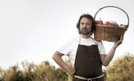 Landwirt mit einer ?kologischen Ernte des Gem?ses in einem Korb nahe den Gartenbetten im Sommer stockfotos