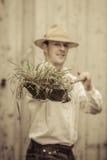 Landwirt mit einer Schaufel voll vom Gras Stockfoto