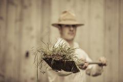 Landwirt mit einer Schaufel voll vom Gras Stockbild