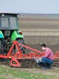 Landwirt mit Laptop und Traktor Stockbilder