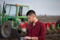 Landwirt mit Laptop und Traktoren lizenzfreie stockfotos