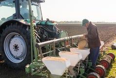 Landwirt mit strömendem Sojabohnenölsamen der Dose für das Säen erntet am agricultura stockfotos