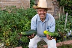 Landwirt mit zwei enormen Zucchinis Lizenzfreie Stockbilder