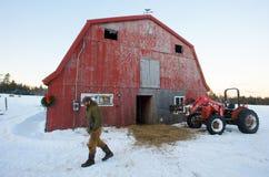 Landwirt, roter Stall und roter Traktor Stockbild