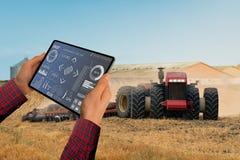 Landwirt steuert einen autonomen Traktor lizenzfreies stockfoto