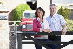 Landwirt und Frau, die über Bauernhof-Gatter schauen Stockbild
