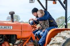 Landwirt und Kind, die einen Weinlesetraktor reiten Lizenzfreie Stockfotografie