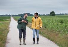 Landwirte, die auf Landstraße gehen stockbilder